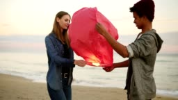 Young multiethnic couple holding red paper lantern before launching. Romantic date on the beach. Attractive woman together with her african boyfriend holding lantern with fire before to let it fly