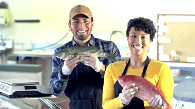 vidéos et rushes de jeune couple multi-ethnique au marché de poissons - vendeur
