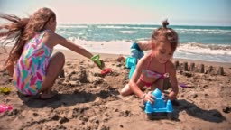 Young multi-ethnic friends building sandcastles on beach in summer