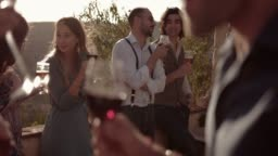 Young multi-ethnic friends drinking wine and beer at rustic party