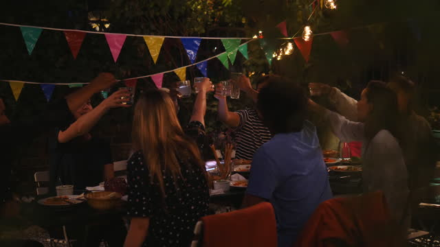 young multi-ethnic friends raising celebratory toast during dinner party in back yard at night - community stock videos & royalty-free footage