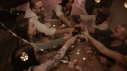 Young multi-ethnic friends toasting at elegant rustic dinner party