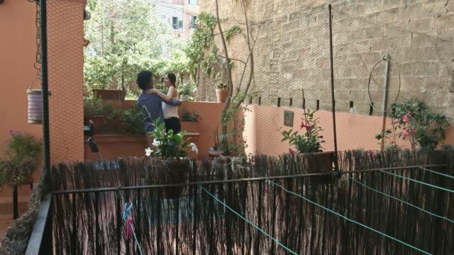 vídeos y material grabado en eventos de stock de joven pareja feliz multiétnica bailando en una terraza del apartamento - variación