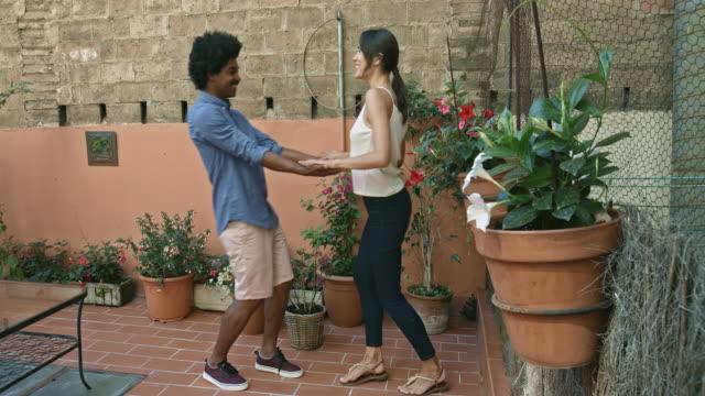 vidéos et rushes de jeune couple heureux multiethnique s'amuser danser dans une appartement terrasse en vacances - terrasse