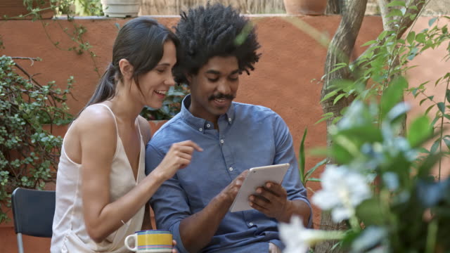 young multi-ethnic happy couple playing with digital tablet in an apartment terrace on holidays - patio stock videos & royalty-free footage