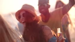 Young multi-ethnic hipsters dancing and drinking beer at beach party