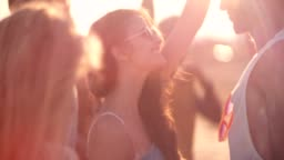 Young multi-ethnic hipsters dancing at summer beach music festival
