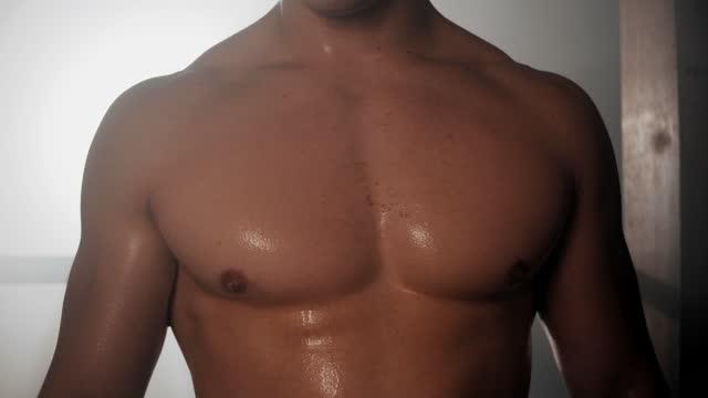 slow motion junger muskulöser bodybuilder schwitzt nach dem training - nur männer stock-videos und b-roll-filmmaterial