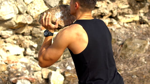 young muscular bodybuilder training outdoors - picking up stock videos & royalty-free footage