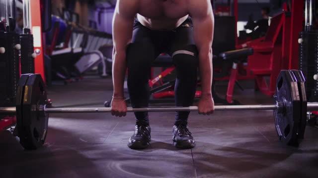 vídeos de stock, filmes e b-roll de jovem homem musculoso fazendo os exercícios pesados mortos-elevador no ginásio, conceito de lifestyle esporte e musculação - equipamento para exercícios