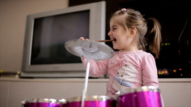 young music talent,little girl playing drums toy at home