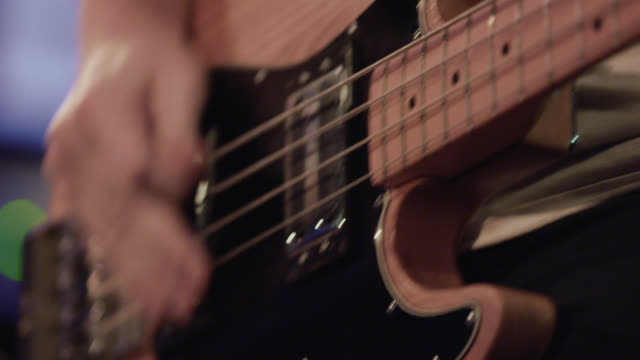vídeos de stock e filmes b-roll de young musician picks hard and fast on bass guitar - punk