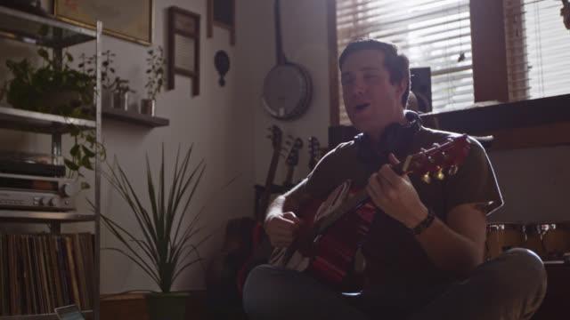 vídeos y material grabado en eventos de stock de ms slo mo. young musician plays acoustic guitar and sings in modern apartment studio. - guitarrista