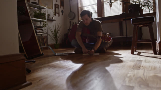 WS SLO MO. Young musician plays acoustic guitar and writes in notebook on living room floor.