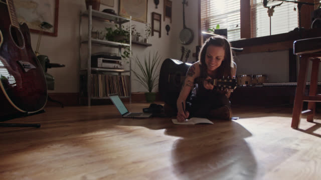 vídeos de stock, filmes e b-roll de ws. young musician writes in notebook and picks acoustic guitar in modern apartment. - interior