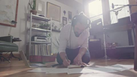 ws slo mo. young musician writes in notebook as he listens to music in headphones on apartment floor. - musikinstrument bildbanksvideor och videomaterial från bakom kulisserna