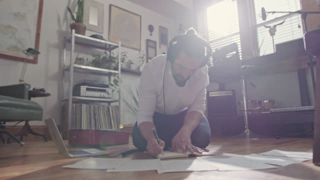 ws slo mo. young musician writes in notebook as he listens to music in headphones on apartment floor. - cuffia attrezzatura per l'informazione video stock e b–roll