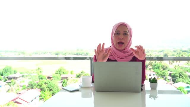 vidéos et rushes de jeunes femmes d'affaires musulmanes en tissu religieux en hiver en utilisant un ordinateur portable et souriant pendant le travail, présentation à la caméra pour montrer les voyages verts locaux sur le balcon d'un hôtel, appartement parmi la scène - non urban scene