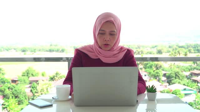 vidéos et rushes de ํles jeunes femmes d'affaires musulmanes en tissu religieux en hiver en utilisant un ordinateur portable et des affaires de travail pendant le travail, présentation hors du bureau sur le balcon d'un hôtel, appartement parmi la scène verte, vue non - non urban scene