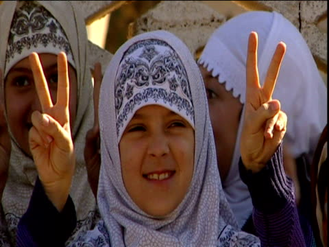 Young Muslim girl in headdress smiles and holds hands in peace sign Iraq