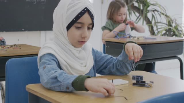 young muslim girl working at her school desk - school science project stock videos & royalty-free footage