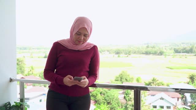 vidéos et rushes de jeune musulman en tissu religieux en hiver à l'aide d'un smartphone pendant les vacances, vacances sur le balcon d'un hôtel, appartement au milieu de la scène verte, vue non urbaine - non urban scene