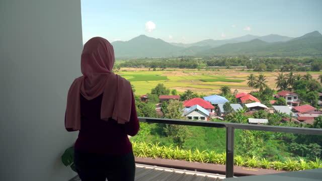 vidéos et rushes de jeune musulman en tissu religieux en hiver à pied de la chambre pour voir vue sur le paysage pendant les vacances, vacances sur le balcon d'un hôtel, appartement au milieu de la scène verte, vue non urbaine - non urban scene
