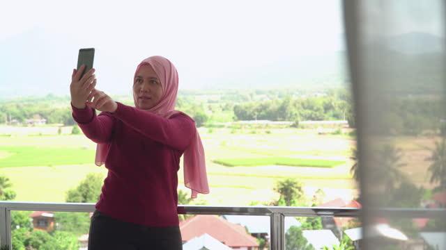 vidéos et rushes de jeune musulman en tissu religieux en hiver à l'aide d'un smartphone, selfie pendant les vacances, vacances sur le balcon d'un hôtel, appartement au milieu de la scène verte, vue non urbaine - non urban scene