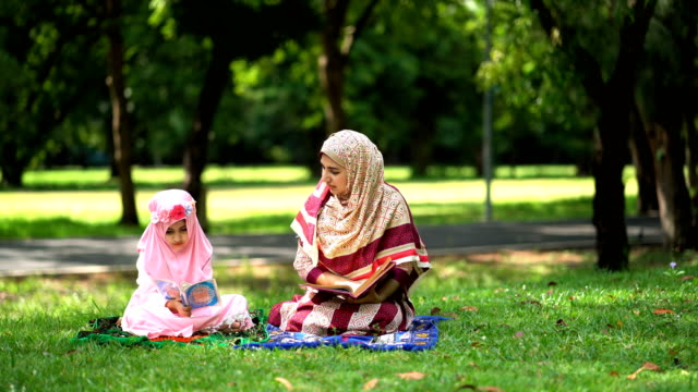 4k young muslim mother opening quran and teaching her daughter to read - koran stock videos & royalty-free footage