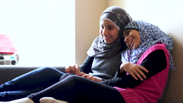 young muslim sisters laughing with each other in their home - homework stock videos & royalty-free footage
