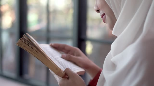 young muslim woman in head scarf reading ancient book in coffee shop. - student leadership stock videos & royalty-free footage