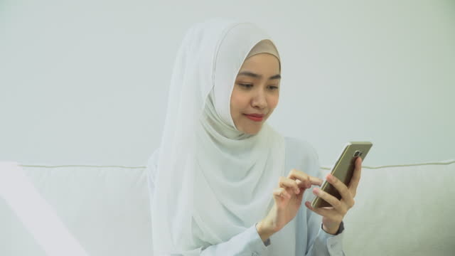 vídeos de stock e filmes b-roll de young muslim woman in hijab typing phone - 30 34 years