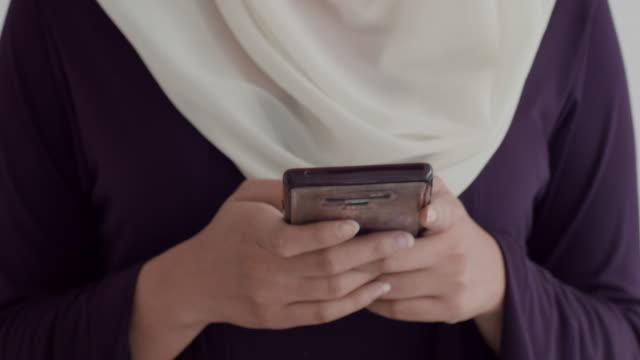 vidéos et rushes de jeune femme musulmane dans le téléphone de dactylographie de hijab - foulard