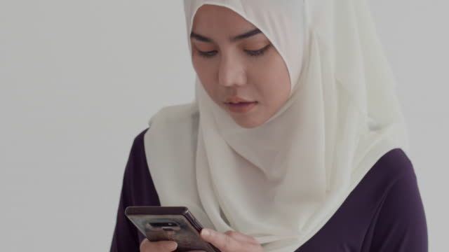 young muslim woman in hijab typing phone - asian chance stock videos & royalty-free footage