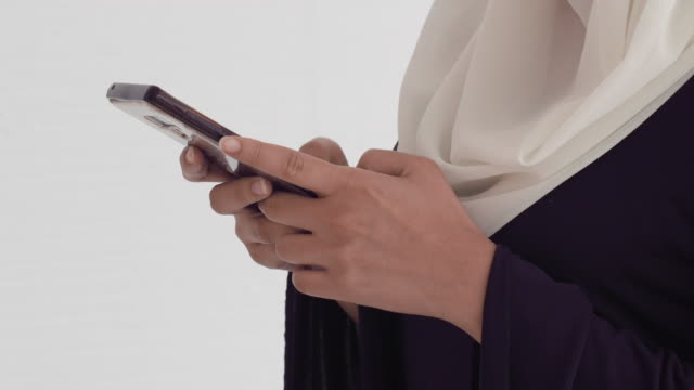 young muslim woman in hijab typing phone - handheld stock videos & royalty-free footage