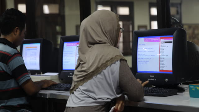 a young muslim woman is wearing a headscarf and is doing research in a library in yogyakarta on java - person in further education stock videos & royalty-free footage