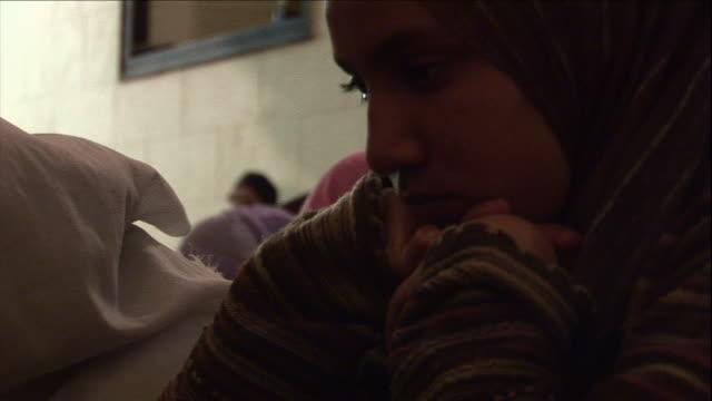 vidéos et rushes de a young muslim woman seems contemplative as she worships. - mosquée