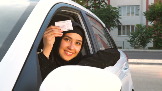 young muslim woman showing her driving licence in car - religion stock videos & royalty-free footage