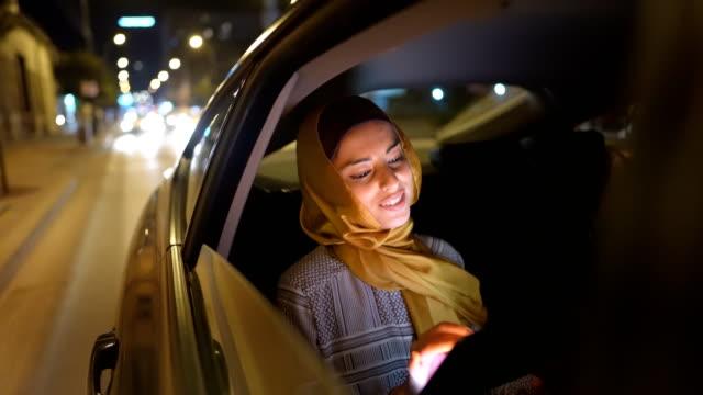 ung muslimsk kvinna som sitter i baksätet och använder tablett - yellow taxi bildbanksvideor och videomaterial från bakom kulisserna