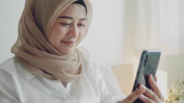 Jeune femme musulmane prenant la photo de selfie sur le téléphone portable à la chambre à coucher