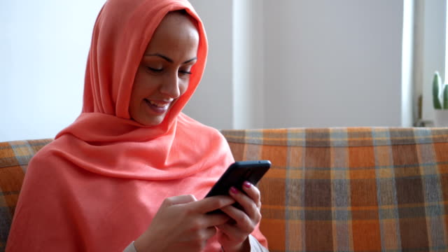 Young Muslim woman texting messages