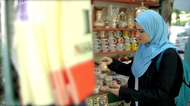 Young Muslim woman with backpack on summer vacation,watching and buying souvenirs for family