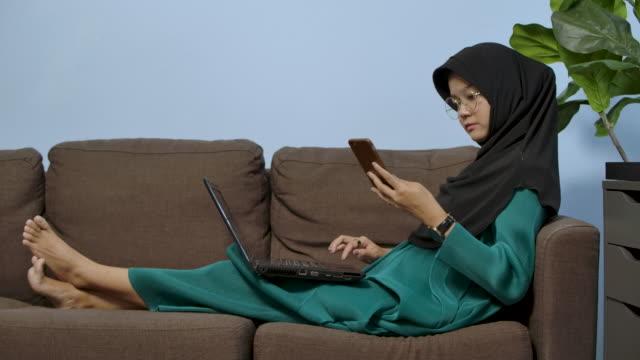 vidéos et rushes de une jeune femme musulmane travaille de la maison avec son ordinateur portable et son smartphone pendant le coronavirus de quarantaine covid 19 - vêtement religieux