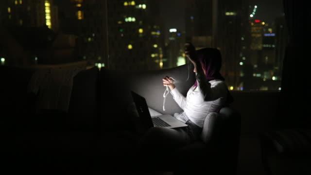 vídeos de stock, filmes e b-roll de jovem mulher muçulmana trabalhando até tarde em kuala lumpur - embaraçado