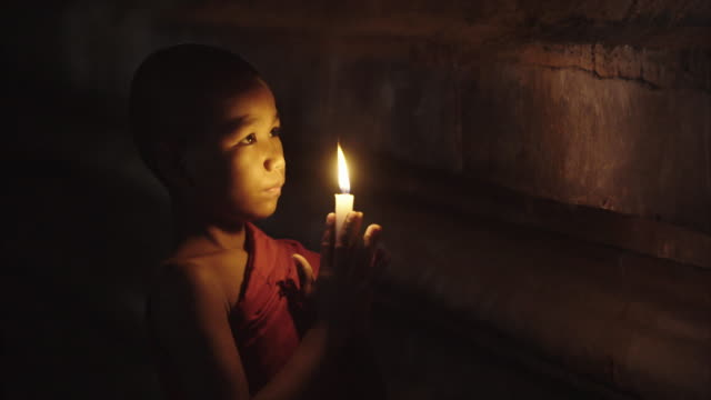 young myanmar monk praying holding lit candle in the dark - buddhismus stock-videos und b-roll-filmmaterial