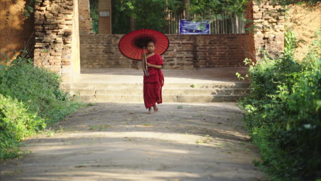 young myanmar monk walking with red umbrella