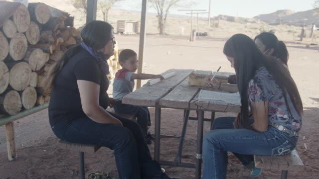 若いネイティブアメリカンナバホ兄弟は、covid-19パンデミックの間に一緒にホームスクーリングを一緒に宿題をしている屋外テーブルで自宅の前でモニュメントバレーで - インディアン居留地点の映像素材/bロール
