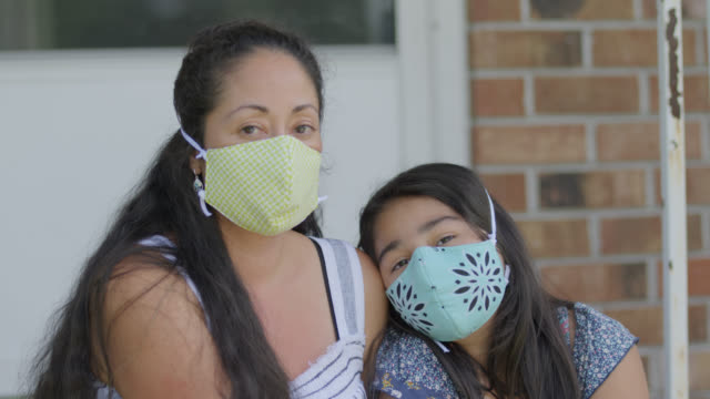 slo mo cu young native-american daughter rests her head on her mother while wearing protective face masks - protection stock videos & royalty-free footage