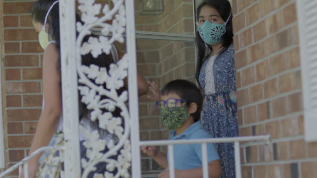 ms young native-american family walk of their front door wearing protective face masks - veranda stock videos & royalty-free footage