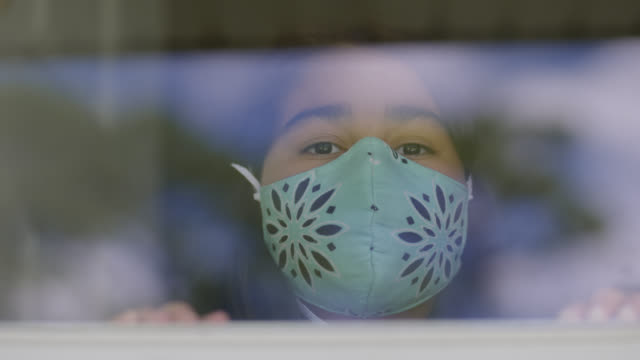 cu young native-american girl wearing protective face mask looks out of window - patient stock videos & royalty-free footage